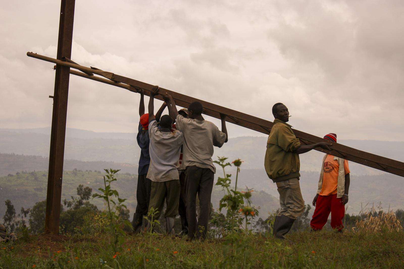 Un gruppo di operai è al lavoro per la sistemazione di un traliccio della corrente nell'area rurale nei dintorni di Murambi, Provincia Settentrionale.