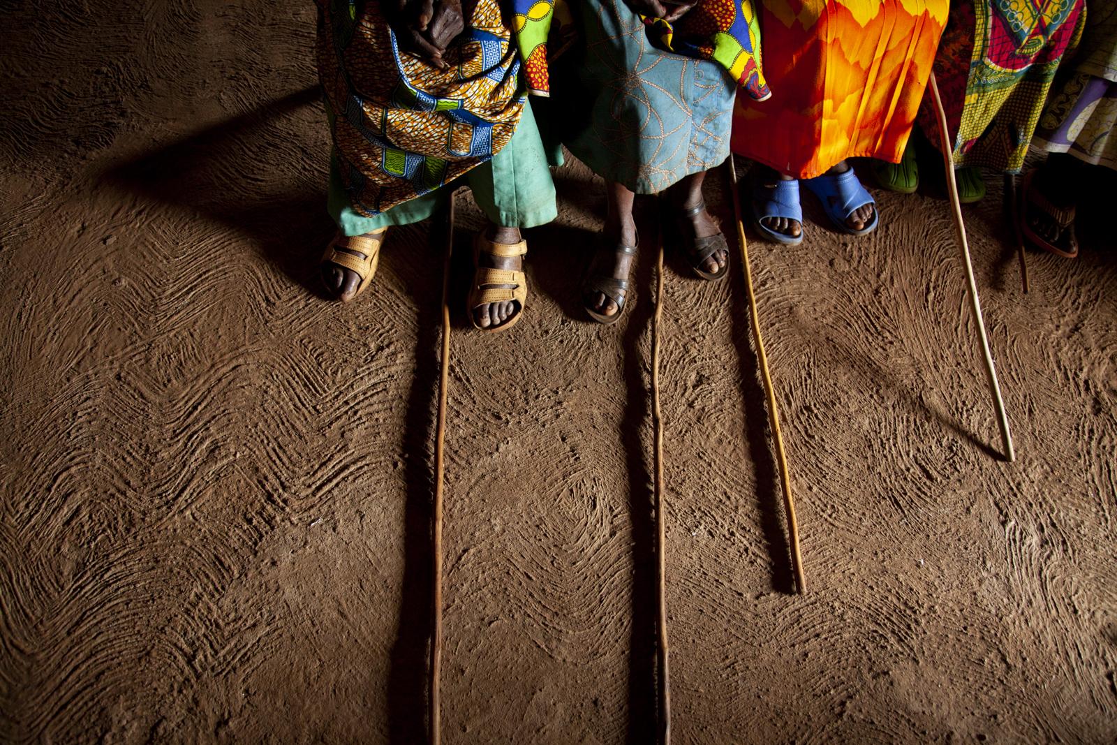 Gli anziani del villaggio hanno percorso molta strada per presenziare alla riunione nella capanna tradizionale di Rutongo. Trovato un posto a sedere, posano i bastoni a terra.